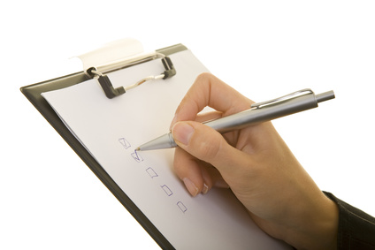Hand mit Stift macht Häkchen auf einem Klemmbrett